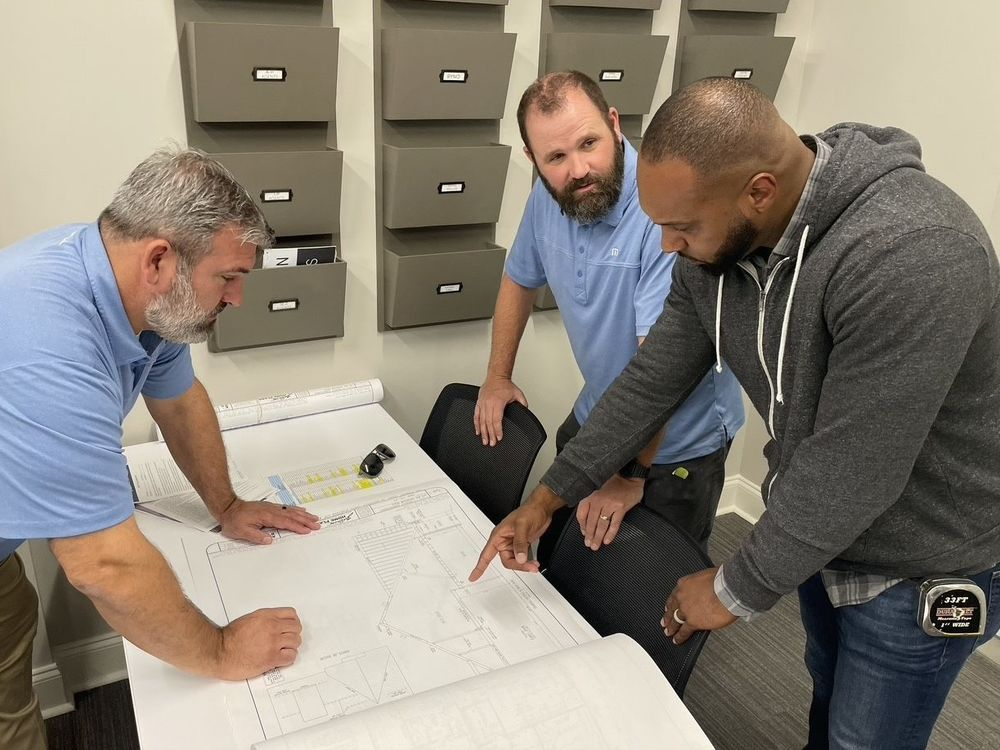 Todd Roaten, David Lomax, and Johnnie Tubbs of Regency Homebuilders look at building plans for a project. Regency Homebuilders was voted the top workplace among small businesses. Regency Homebuilders